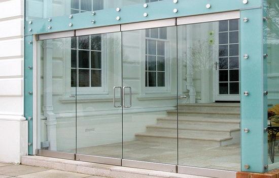 Двери стеклянные наружные с зажимным профилем сверху и снизу
