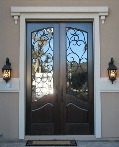 Двухстворчатая металлическая входная дверь со стеклом и ковкой, отделанная деревом